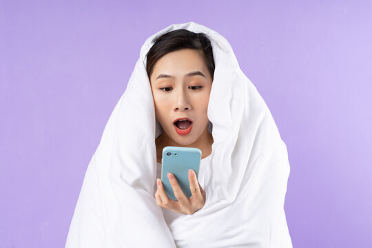 Asian woman curled up in blanket on purple background