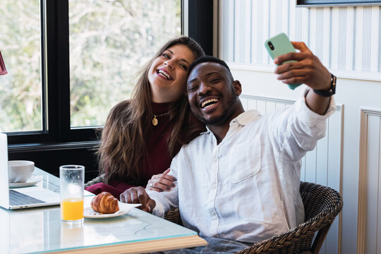 Cheerful multiethnic couple using laptop at home while taking a selfie