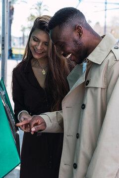 Happy multiethnic couple using ATM machine on street
