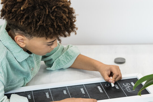 Attentive black schoolboy writing on blackboard while studying at home