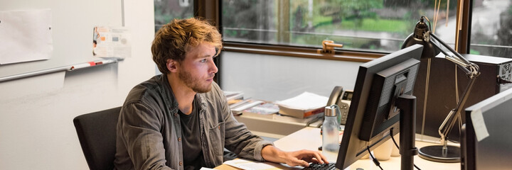 Fototapeta Young phd student studying writing final paper for exam at university. Working man at office desk typing at desktop computer in library room. obraz