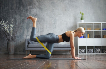 Fototapeta Young and sporty girl in sportswear is doing exercises in home interior using resistance band. Fit and slender blond woman goes in for sports and fitness. Healthcare, fat burn and wellness. obraz