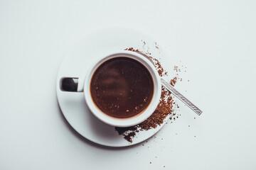Taza de café con galletas y granos molidos en fondo blanco