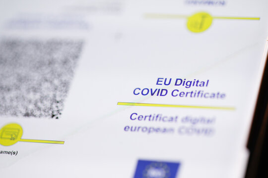 Shallow depth of field (selective focus) details with an European Digital COVID certificate on the display of a mobile device.