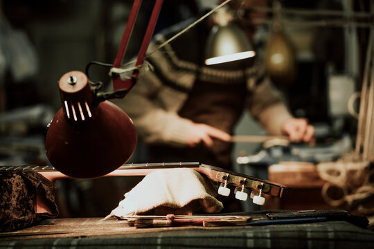 Crop unrecognizable luthier polishing wooden detail at workbench