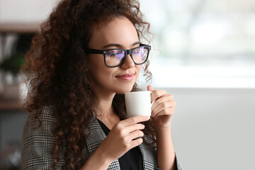 Beautiful young woman drinking coffee in kitchen