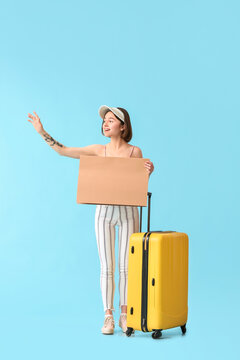 Young woman with cardboard and suitcase hitchhiking on color background