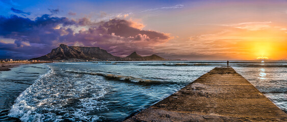 Picturesque and colourful sunset scene of Table Mountain and The Atlantic Ocean. A jetty reaches out to the cool blue sea to inspire a sense of adventure. A stunning tourist destination - Cape Town