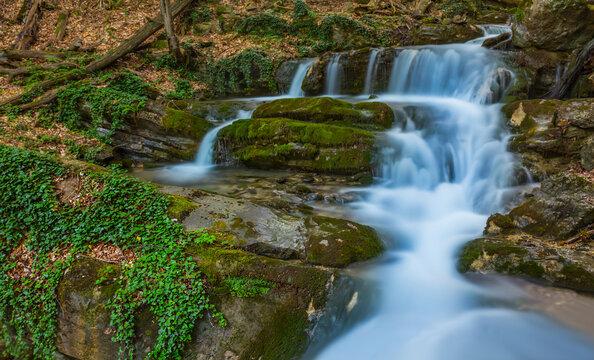 closeup blue waterfall rushing through mountain canyon