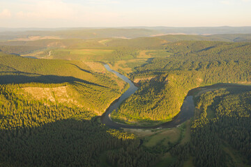 Aerial view of river Agidel in the morning. River flowing among mountains covered by forest