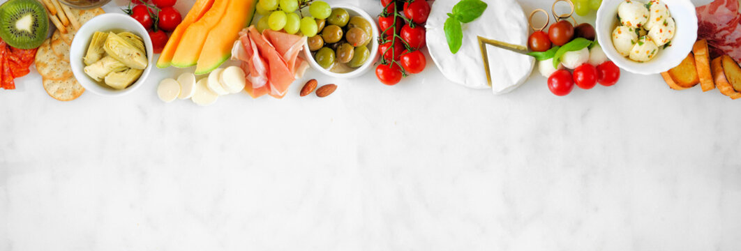 Italian theme charcuterie top border against a white marble banner background. Assortment of cheese, meat and fruit appetizers. Above view with copy space.