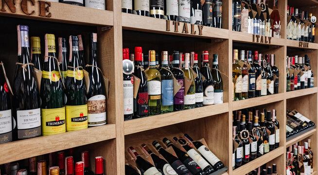 Minsk, Belarus - July 03, 2021: Various wine bottles sale on the wooden shelf in a supermarket shop.