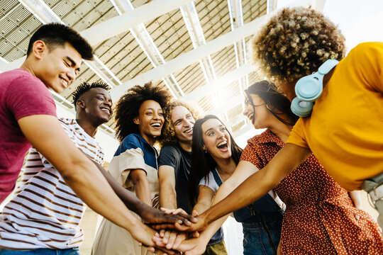 Multiracial happy friends with hands in stack. Multi-ethnic diverse group of college students joining their hands. Stacking hand concept, community, unity and teamwork concept
