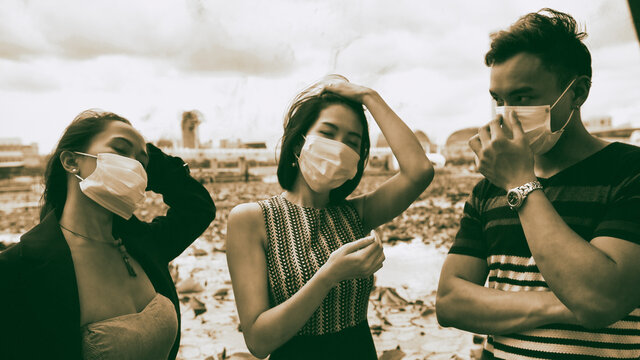 Three asian young friends standing outdoor in the city talking and wearing face masks in covid coronavirus pandemic