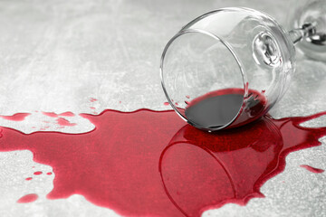 Overturned glass with red wine spill on grey table, closeup