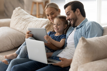 Fototapeta Happy family with little daughter having fun with modern devices, sitting on cozy couch together, smiling mother and father with adorable child girl looking at tablet screen, watching funny video obraz