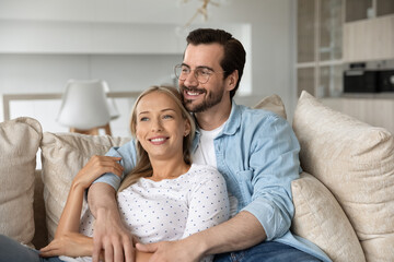 Obraz Dreamy happy young couple hugging, relaxing on couch together, smiling woman and man in glasses looking to aside in distance, visualizing good future planning, enjoying lazy leisure time on sofa - fototapety do salonu