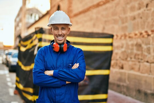 Young caucasian worker smiling happy wearing uniform at the city.
