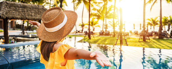 Fototapeta Young woman traveler relaxing and enjoying the sunset by a tropical resort pool while traveling for summer vacation obraz