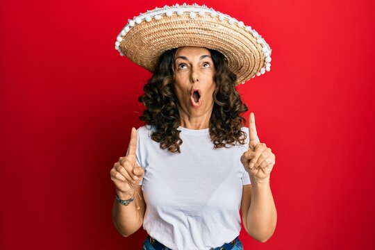 Middle age hispanic woman holding mexican hat amazed and surprised looking up and pointing with fingers and raised arms.