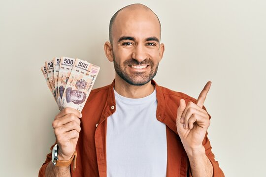 Young hispanic man holding 500 mexican pesos banknotes smiling happy pointing with hand and finger to the side