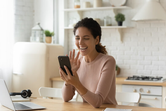 Joyful young hispanic caucasian woman looking at cellphone screen, enjoying distant web camera call using mobile video call zoom application, involved in pleasant distant conversation in kitchen.