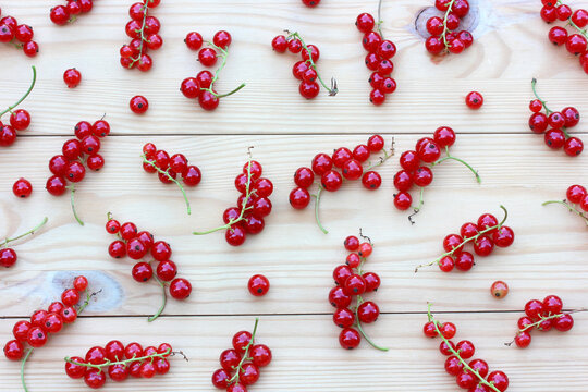 bunches of red currants on a wooden surface.