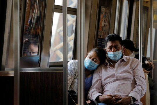 People in masks rest as they ride the subway during the outbreak of the coronavirus disease (COVID-19) in New York City