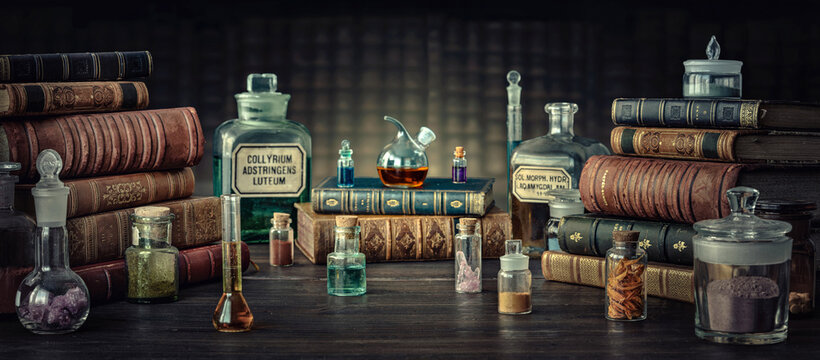 Glass bottles, old books on table of a scientist. Medicine, chemistry, pharmacy, apothecary, alchemy history background. Translation from labels-eyewash astringent, morphine hydrochloride and almonds.