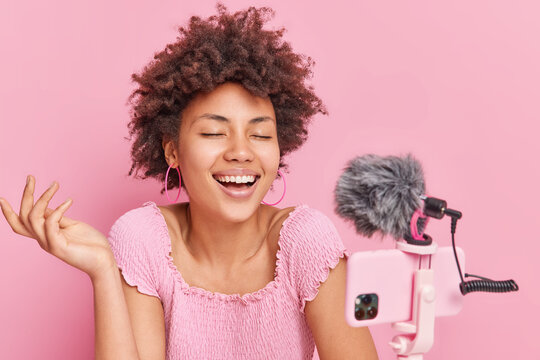 Joyful Afro American female blogger smiles broadly keeps eyes closed has funny talk with subscribers tells anecdotes dressed casually isolated over pink background makes video chat or conference call