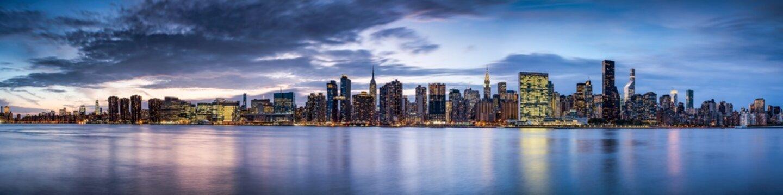 Manhattan skyline panorama along the East River at night, New York City, USA
