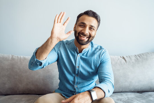 Headshot portrait of handsome indian man with friendly smile waving to camera