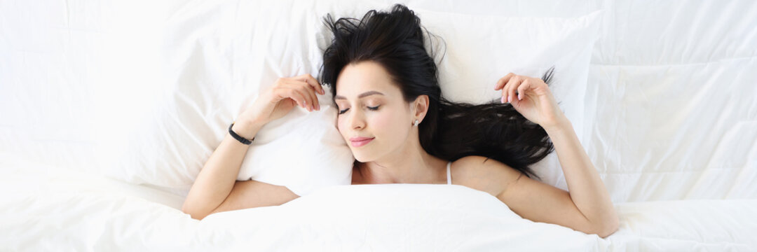 Young brunette woman sleeping in white bed top view