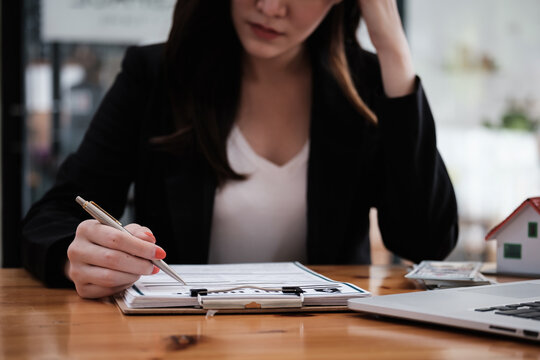 A stressed woman signs a contract to cancel her rent apartment and pay an outstanding payment.