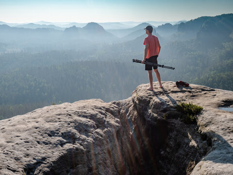 Barefoot man in red t-shirt stay with tripod in hand on rocky viewpoint and looking