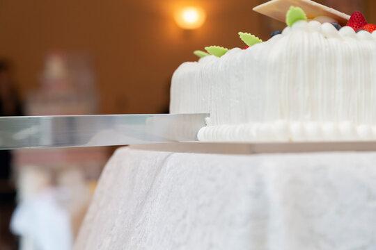 Cutting a wedding cake with a knife