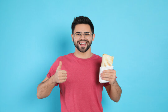 Happy young man with tasty shawarma showing thumb up on turquoise background