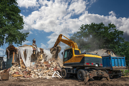Hydraulic Excavator Breaks House. Building Demolition or Destruction for New Construction.