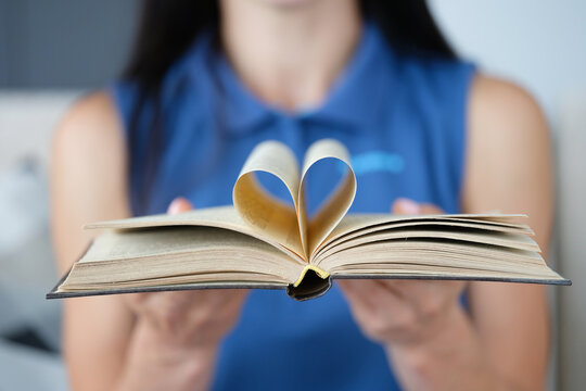 Woman is holding book with a page in shape of heart folded in center