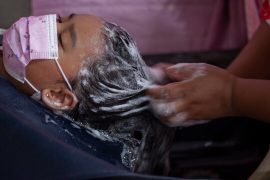 Asian little girl wearing a mask to prevent the Novel Coronavirus disease starting in 2019 (Covid-19) that is currently spreading while let the beautician wash their hair at the beauty salon.