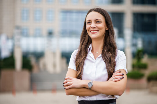 Portrait of happy businesswoman in front of company building.