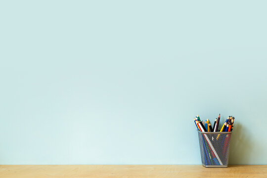Home office desk table background. Empty wall with wooden table with stationery, pencils for work or study. Copy space