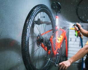 Obraz Bicycle mechanic. He is cleaning, washing bikes. Road bikes. - fototapety do salonu