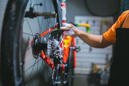 Bicycle mechanic. He is cleaning, washing bikes. Road bikes.