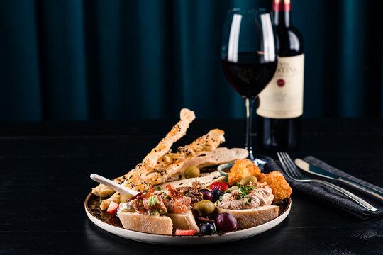 Italian antipasti wine snacks set. Brushettas, cheese variety, Mediterranean olives and wine in glasses over black grunge background