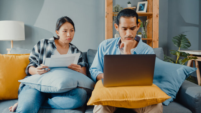 Asia young couple man and woman sit on couch serious focus on laptop computer check document paper pay bills online plan budget expense in living room. Young married asian debt loan problem concept.