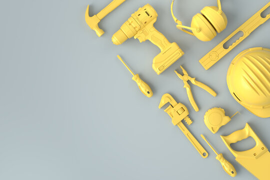Top view of monochrome construction tools for repair on grey and yellow