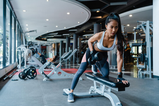 Beautiful young Asia lady exercise doing lifting barbell fat burning workout in fitness class. Athlete with six pack, Sportswoman recreational activity, functional training, healthy lifestyle concept.