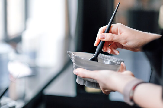 Hairdresser holding bowl with hair dye in beauty salon