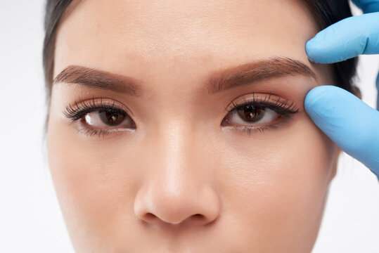 Close-up image pf plastic surgeon touching brow area of young woman before making injection of botox